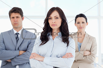 Three serious business people crossing their arms in a well-lit