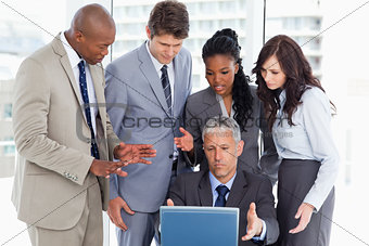 Business team seriously talking in front of a laptop