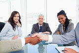 Three smiling co-workers looking at two business people shaking