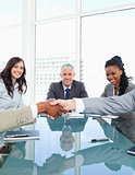 Businesswomen smiling during a meeting while looking at colleagu