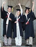 Smiling graduates raising arm