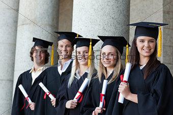 Graduates posing in single line