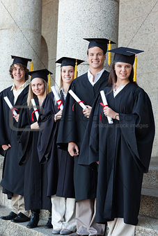Happy graduates posing in single line