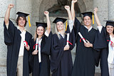 Smiling graduates posing while raising arms