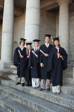 Laughing graduates posing the thumb-up