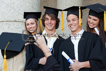 Close-up of a graduate taking a picture of her friend