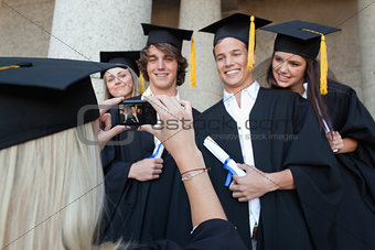 Close-up of a female graduate taking a picture of her friend