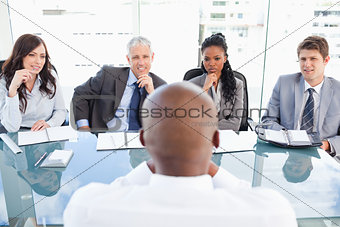 Four business people sitting at the desk while attentively liste