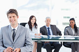 Smiling young businessman sitting in front of his team and looki