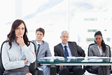 Confident businesswoman sitting with her hand on her chin while