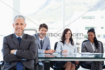 Mature businessman sitting with his arms crossed while his team