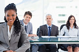 Serious businesswoman sitting in front of her team while smiling