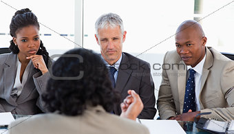 A business team is earnestly listening to an associate