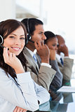 Smiling call centre agent looking at the camera while working ha
