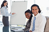 Two smiling employees sitting at a desk in a meeting room during
