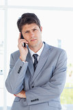 Serious businessman making a call while looking at the camera