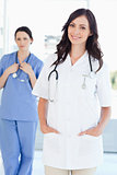 A nurse standing upright while her colleague is standing behind