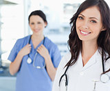 Smiling nurse standing upright while leaning her head to the sid