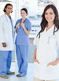 Smiling female doctor standing upright with her hands in her poc