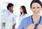 Confident nurse standing upright accompanied by her team in the