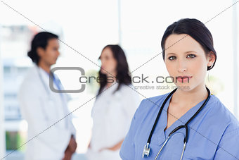 Calm nurse standing upright with her stethoscope around her neck