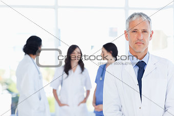 Mature doctor standing in the foreground and accompanied by his