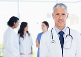Mature and calm doctor standing upright in front of his medical