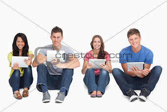 A group of people sitting beside each other with tablets while l