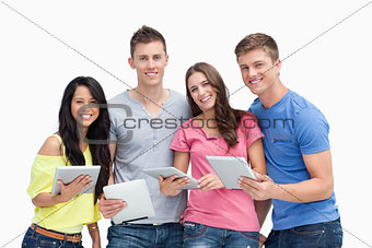 A smiling group with tablet pc's in hand as they look at the cam