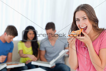 A woman in front of her friends as she is about to eat a slice o