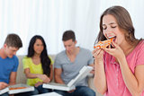 A woman about to eat a slice of pizza with her friends behind he