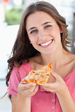 Close up of a woman smiling with a piece of pizza and looking at