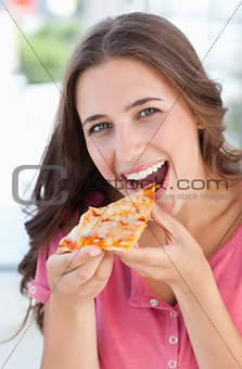 A woman about to eat a piece of pizza as she looks at the camera