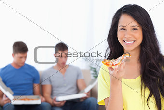 A woman holding pizza in her hand as her friends sit behind her