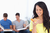 Woman smiling as she looks at the pizza slice with her friends b
