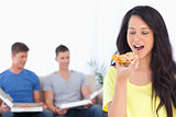 Woman about to eat a pizza slice as her friends sit behind her