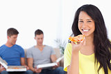 Woman smiling and looking at the camera as she holds pizza