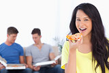 Smiling woman about to eat some pizza with her friends in the ba