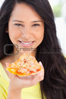 Close up of a woman smiling holding pizza to her mouth