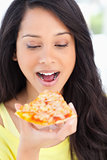 Close up of a woman looking at the slice of pizza she is about t