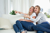 Girls laughing on the couch as they watch tv