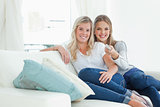 A pair of girls with a tv remote as they look at the camera