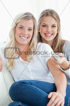 Close up of laughing sisters sitting on the couch