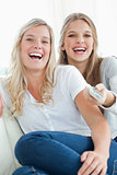 Close up of laughing girls watching tv