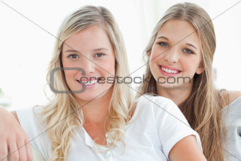 A pair of girls smiling as they look at the camera