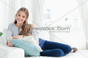 A smiling girl lying on the couch facing the camera