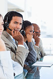 Young call centre employee surrounded by his business team