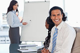 Young employee smiling during a presentation while his team is w