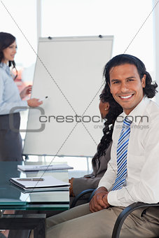 Smiling businessman sitting at a desk while listening to a prese