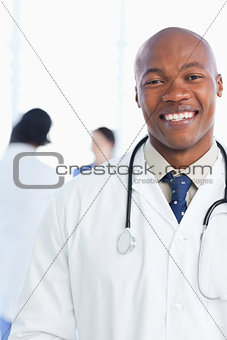 Medical intern showing a beaming smile in front of his team
